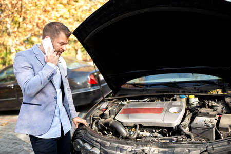 Attractive young upset man making a call while his car broke down on vacation