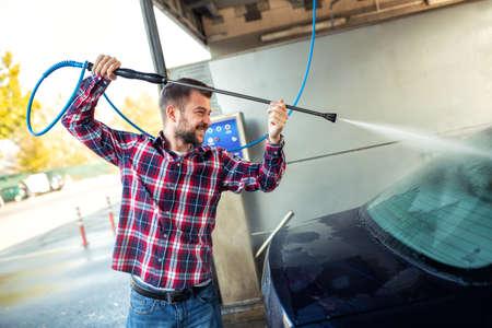 Handsome man washing his car using only a spray gun