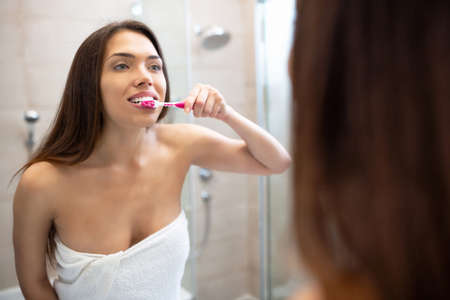 Girl standing in front of the mirror and brushing teeth making that smile appear amazing 版權商用圖片