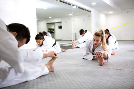 Martial artists doing leg splits while warming up for taekwondo practice, stretching concept