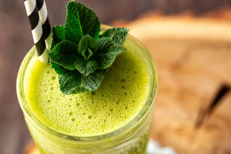 Citrus smoothie viewed in close up and decorated with green leaves, citrus smoothie concept