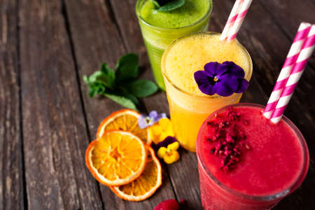 Smoothies for energy boosting and body replenishment with vitamin C placed on the rustic wooden background