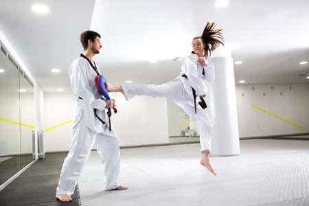 Cute brunette girl doing a leg kick practice while her trainer assists her Reklamní fotografie - 123150831