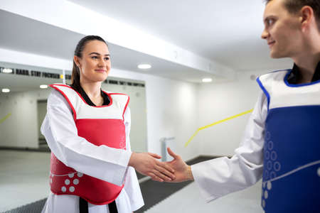 Young woman training martial art of taekwondo with her coach, sportsmanship concept Stock Photo