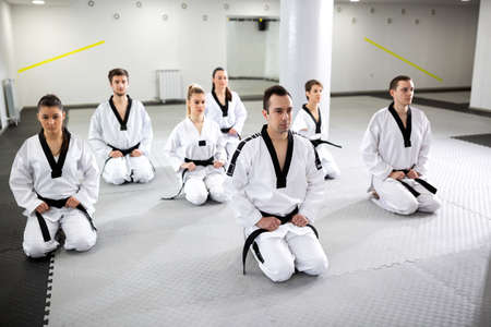 Young woman with physical disability practicing taekwondo sitting on the floor with her martial art colleagues, tolerance and respect concept