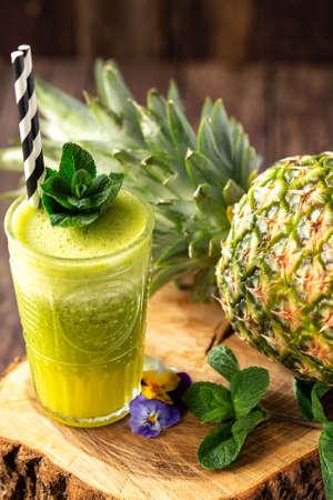 Frullato verde con ananas sullo sfondo posto sul ceppo di legno