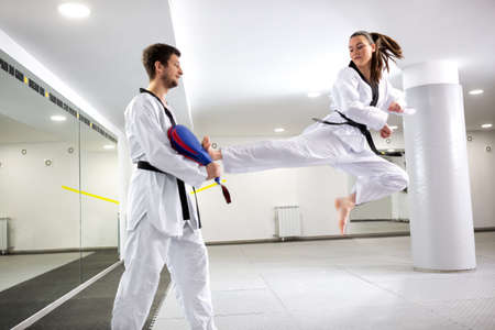 Young girl training martial art of taekwondo performing a kick from a jumping position, physical performance Reklamní fotografie - 123152961