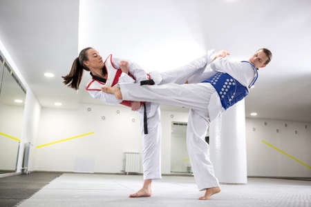 A Guy and a girl in close taekwondo combat training preparing to be more competitive