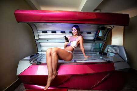 Attractive woman preparing for a sunbed tanning and smiling 版權商用圖片