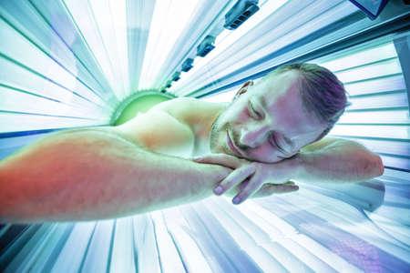 Souriant jeune homme au solarium se détendre en position couchée sur le ventre et profiter