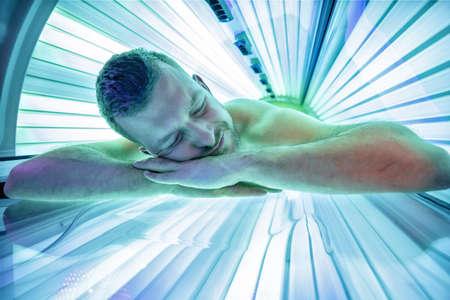 Lächelnder junger Mann im Solarium, der sich beim Liegen auf dem Bauch entspannt und genießt Standard-Bild