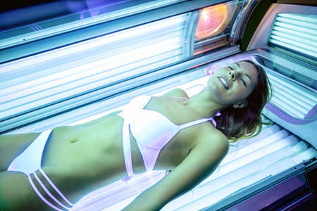 Pretty woman in white bikini lying in tanning booth, tanned skin concept