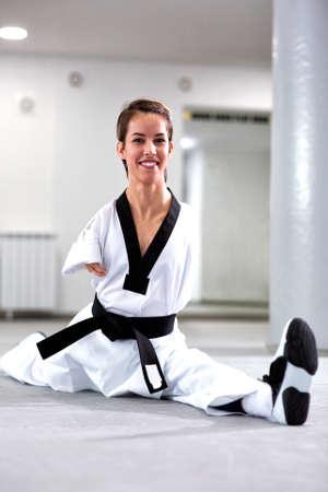 Para-taekwondo athlete doing a leg split while laughing and smiling Stockfoto