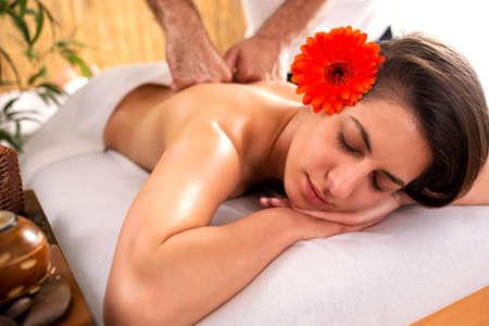 Girl in Zen mode while having a massage relaxing and enjoying