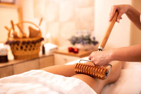 Wooden roller with extended handle applied in body massage, anti-cellulite treatment Stock fotó - 131482096