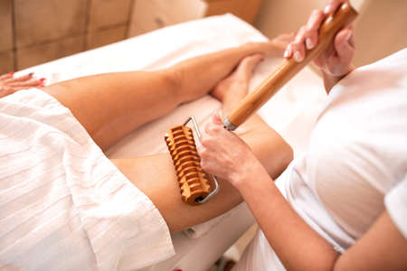 Maderotherapy and thigh massage, anti-cellulite treatment with wooden roller Imagens