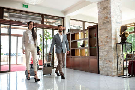 Happy couple entering the hotel pulling their luggage, vacation concept Stok Fotoğraf