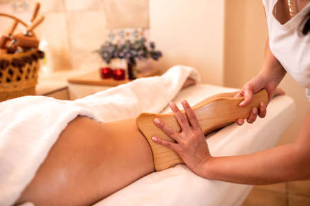 Masseuse holding a hand held wooden massage tool, anti-cellulite massage