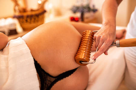 Extended handle wooden roller applied in anti-cellulite therapy, anti-cellulite concept