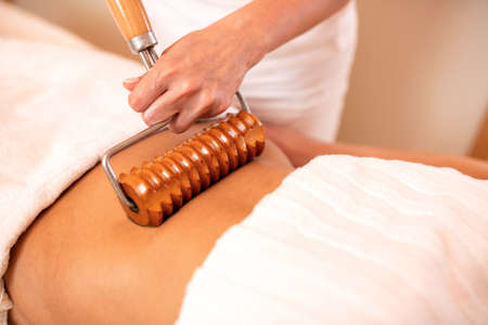Wooden roller with extended handle applied in body massage, anti-cellulite treatment