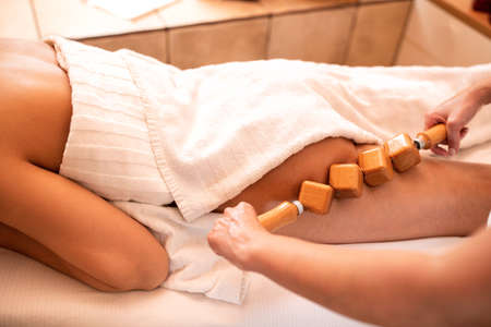 Anti-cellulite massage with special wooden roller that is cubically shaped