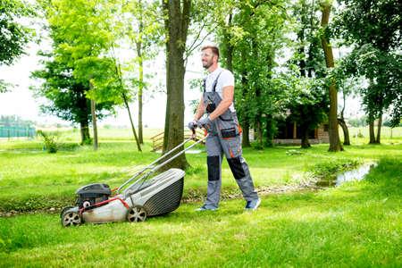 Gärtner mit Rasenmäher bei der Arbeit ausgestattet, Konzept des Rasenmähens