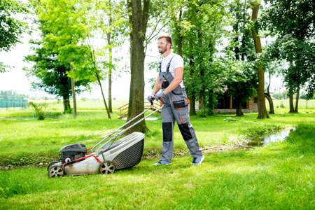 Gardener equipped with lawnmower on the job, concept of lawn mowing