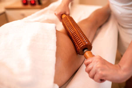 Wooden instruments in maderotherapy applied on the thigh area, anti-cellulite concept Imagens