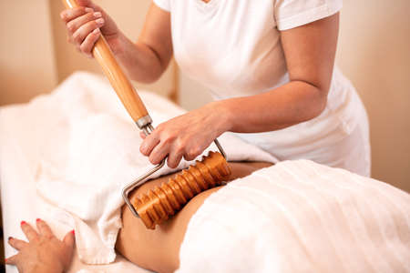 Masseuse massaging the stomach area of her client using a wooden roller