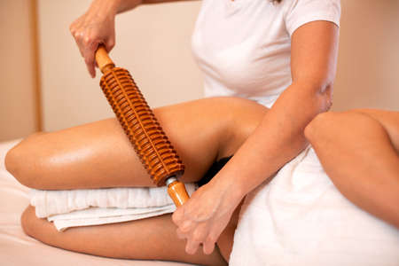 Anti-cellulite massage, wooden roller tool, maderotherapy concept
