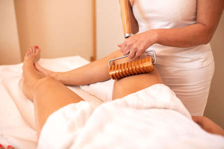 Anti-cellulite therapy with an extended wooden roller tool, maderotherapy Imagens