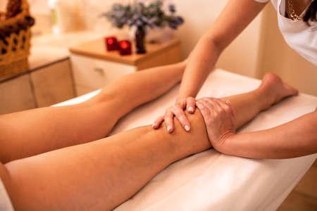 Masseuse working on a calf muscle area; leg massage