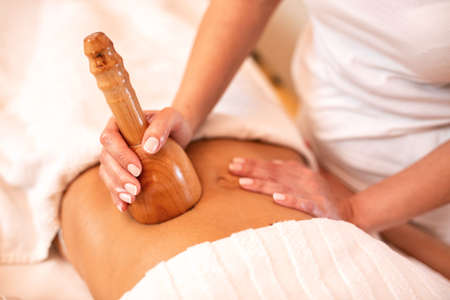 Hand held wooden instrument applied in anti-cellulite therapy on stomach area