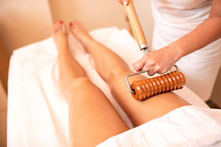 Maderotherapy applied in thigh massage, concept of anti-cellulite Imagens