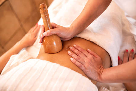 Stomach massage with hand held wooden tool, relaxation concept