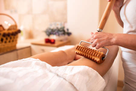 Anti-cellulite therapy with an extended wooden roller tool, maderotherapy Foto de archivo