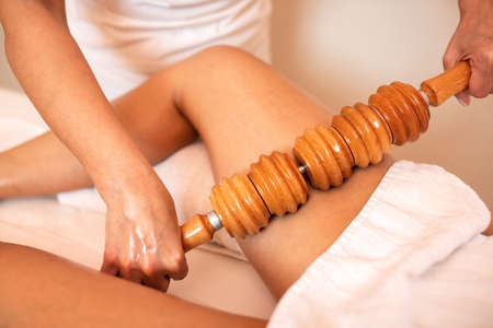 Maderotherapy with a wooden roller, thigh massage concept