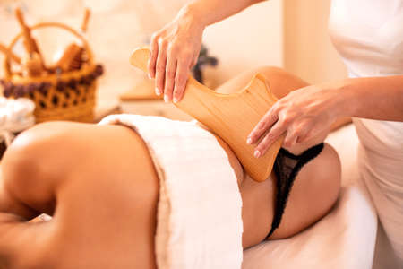 Anti-cellulite maderotherapy massage with wooden instruments, beauty concept Imagens