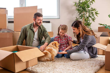 Young couple and their child playing with dog while unpacking