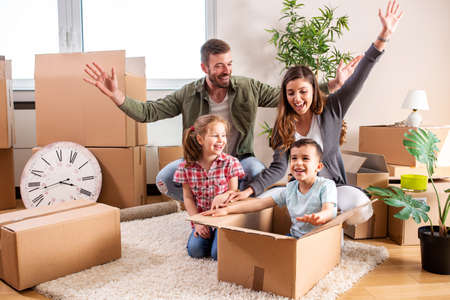 Happy family moving in their new home and having a playtime with their children, concept of having fun