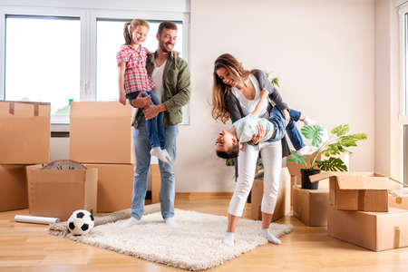 Young couple with their children moving in a new home and being happy about it Stockfoto