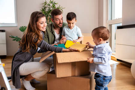 Young couple unpacking boxes with their two sons, moving in concept