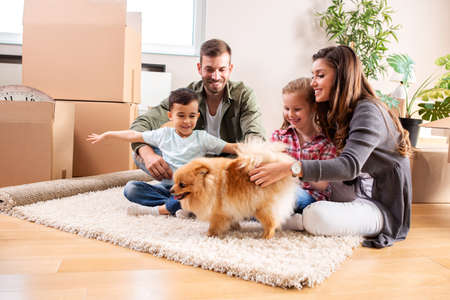 Family of four with their pet dog on the rug of the new apartment having fun Stockfoto