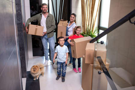 Family in the hall of their home with their dog moving in