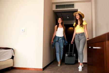 Sexy young women arriving in a hotel room, travel concept