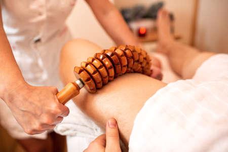 Thigh massage with a flexible wooden roller, concept of leg massage