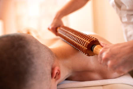 Young man having a neck massage with a wooden roller