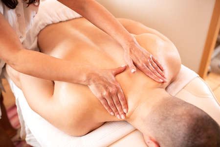Muscular man lying on his chest while having a massage, concept of enjoyment Фото со стока