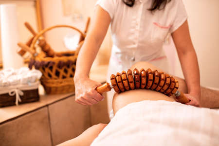 Thigh massage with a wooden roller tool in beauty salon Фото со стока