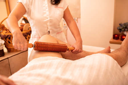 Reducing of muscle tension with a wooden roller massage treatment, leg massage